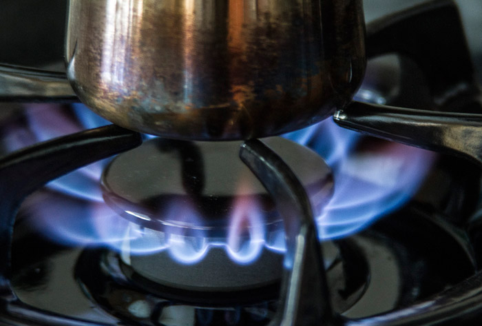 Photo of metal container above burning flame of gas stove top by Noella Ballenger
