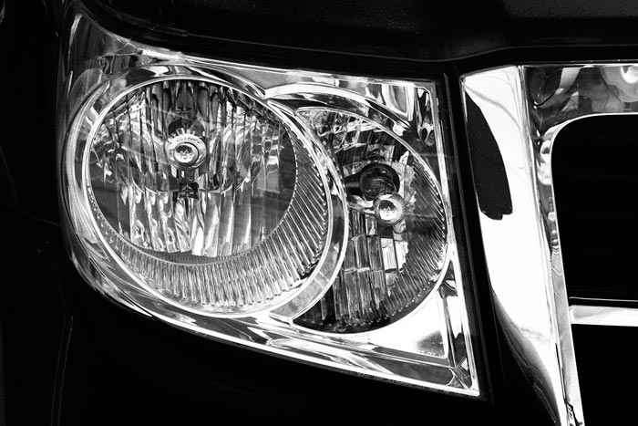 Black and white close-up photo of car grill and headlight by Noella Ballenger