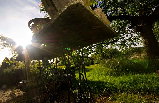 Garden photo tips: rays of the sun coming through the ornate legs of a garden table by Edwin Brosens.