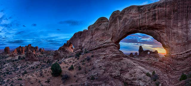 Landscape image of rock formations and rock arche at sunrise in Arches National Park, Utah by Michael Leggero.