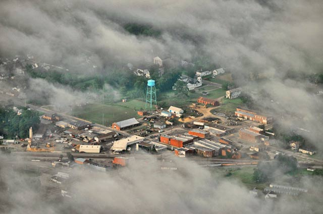 Aerial photo taken through the clouds of a small town with a blue water tower in Virginia by Allen Moore.