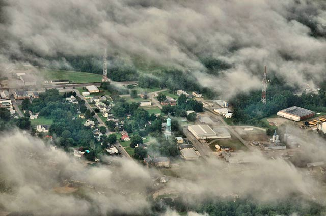 Aerial photo: a small town in Virginia with a blue water tower seen through the clouds by Allen Moore.