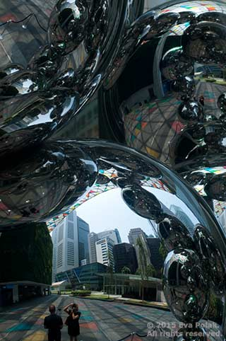 Image of metal sculpture, people and city showing size contrast by Eva Polak.