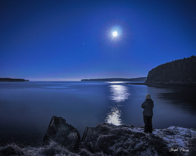 Winter landscape titled Moonstruck - woman standing on shore at night with moon and reflection on water by Joseph Classen.