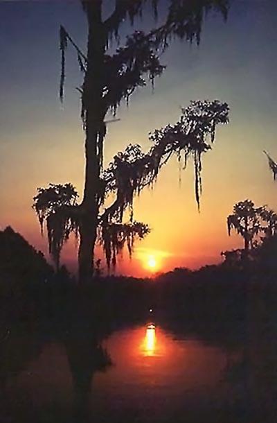 Vibrant orange and yellow sunrise reflected on lake by Willis T. Bird.