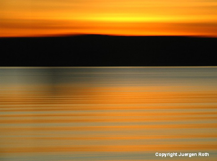 Intentional horizontal camera movement: image of seascape at sunset with orange and gold colors by Juergen Roth.