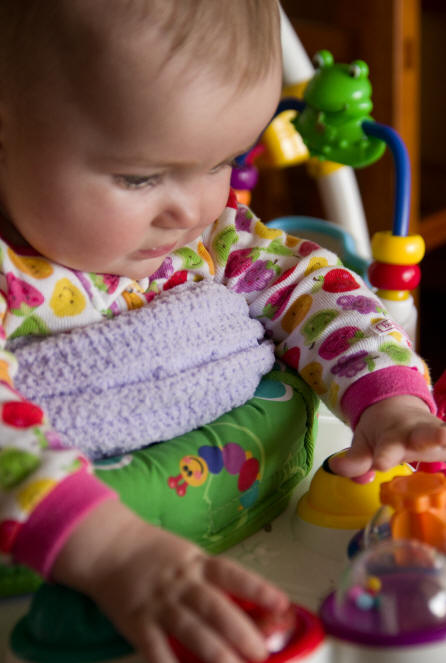 Action image of Baby A playing with her jumpy toy by Elizabeth Powis Fulks..
