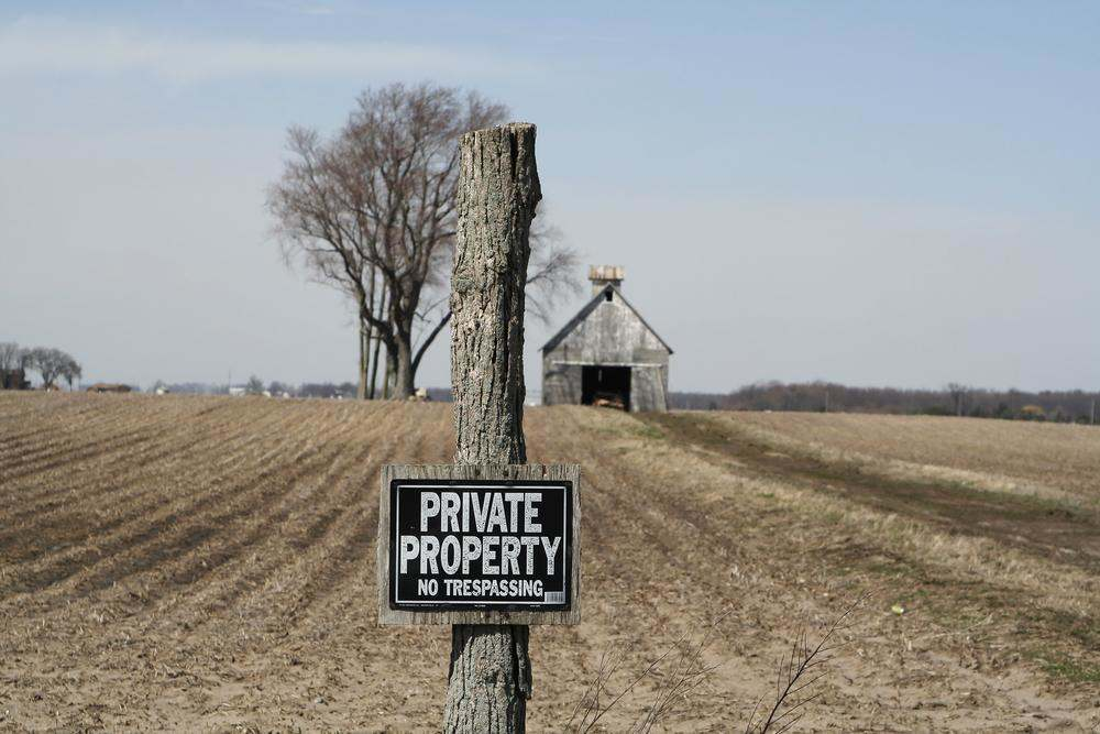 A private property sign posted in front of an abandoned rural property